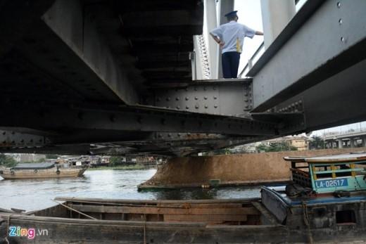 Nhiều sà lan, thuyền chở cát, đá, hàng hóa nóng lòng tìm chỗ trống, nhanh chóng cùng vượt qua gầm cầu khi mực nước triều đang xuống thấp.