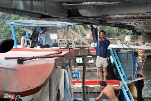 Nhiều tài công và phụ tàu cẩn thận dùng thước đo trước khi cho phương tiện thuỷ đi qua.