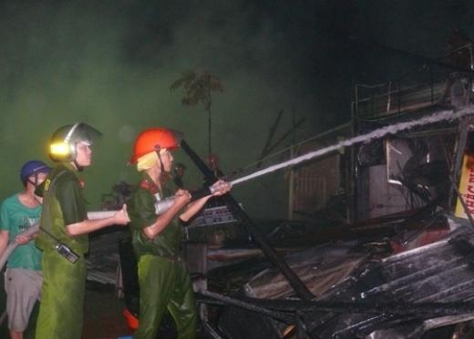 Cảnh sát PCCC nỗ lực phun nước không cho lửa bùng phát trở lại. Ảnh: Xuân Trang