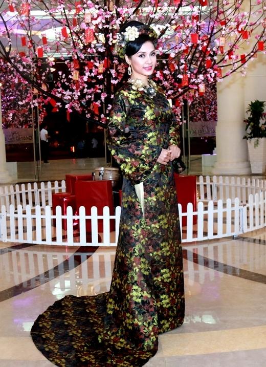 Chiếc áo dài được làm từ chất liệu lụa truyền thống, màu sắc trang nhã, họa tiết sang trọng và kết hợp với các bông hoa mai đính kèm đậm chất mùa xuân. - Tin sao Viet - Tin tuc sao Viet - Scandal sao Viet - Tin tuc cua Sao - Tin cua Sao