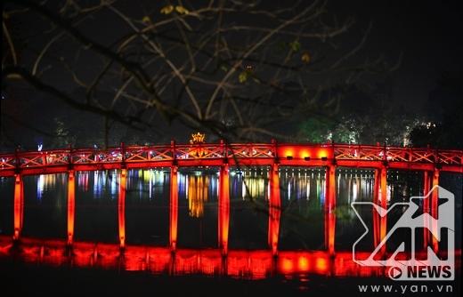 Cầu Thê Húc đỏ rực mờ ảo trên mặt hồ.