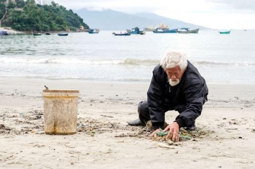 Cụ Mạo đang nhặt rác trên bãi biển Nam Ô. Ảnh: Tấn Lực.
