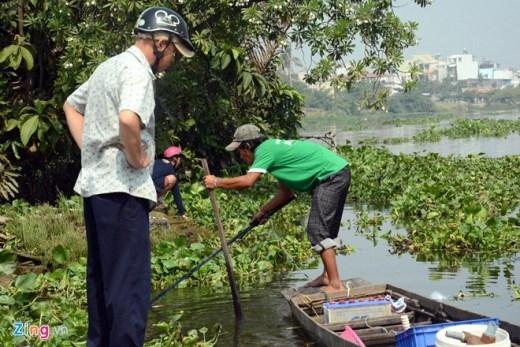 Một người dân vừa phóng sinh cá ngán ngẩm nhìn vào chiếc ghe có hàng chục ký cá của một thanh niên công khai dùng kích điện vớt cá bên bến đò An Phú Đông, quận 12 và Gò Vấp.