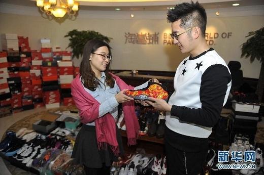 Nhân viên công ty đang xem xét những chiếc giày của anh.Công ty cũng cho biết thêm, cận Tết là thời điểm mà lượng người đến cầm đồ tăng hơn 50% so với thường ngày