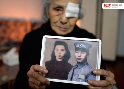 Zhang Shuying, một phụ nữ 93 tuổi, giơ tấm ảnh của chồng và bà. Người chồng tử trận trong cuộc chiến chống phát xít Nhật Bản vào năm 1937. Từ đó tới nay Zhang dồn phần lớn thời gian và tiền vào việc tìm hài cốt của ông.