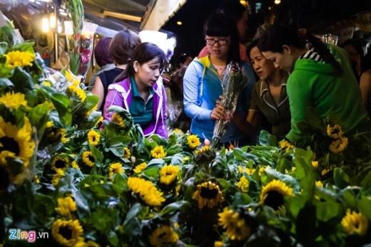 Dù đông đúc, nhưng người mua vẫn cẩn thận lựa chọn từng bông hoa ưng ý. Hoa hướng dương cũng là mặt hàng được yêu thích, với giá bán 1 bó 50.000 đồng.