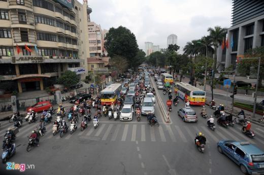 Phố Huỳnh Thúc Kháng các phương tiện tham gia giao thông cũng khá đông đúc, ôtô xếp hàng 3 khiến các xe máy phải len lỏi để vượt qua ngã tư.