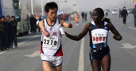 Nữ vận động viên da màu Jacqueline đã giúp một vận động viên khuyết tật uống nước trên một đường chạy ở Taiwan.