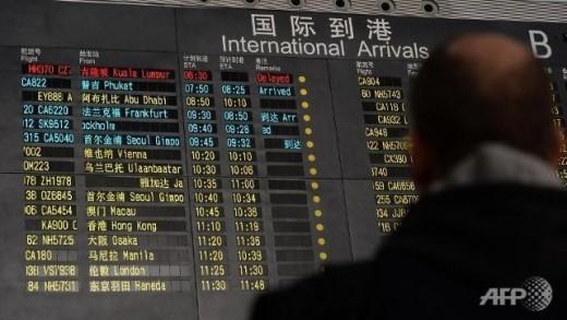 Bảng thông tin tại sân bay quốc tế ở Bắc Kinh thông báo tình trạng của chuyến bay MH370 là 'Chậm giờ' (dòng màu đỏ, hàng đầu bên trái) vào sáng 8/3. Ảnh: AFP
