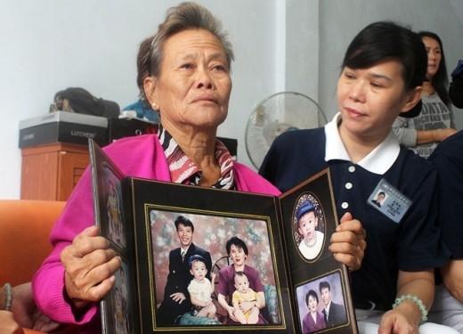 Bà Suharni (người Indonesia) cầm ảnh con trai và vợ của anh. Con trai và con dâu của bà đều là hành khách trên MH370. Ảnh: AFP
