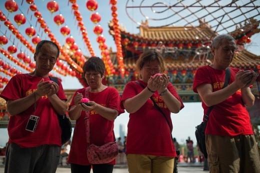 Gia đình của những hành khách người Trung Quốc trên chuyến bay MH370 cầu nguyện cho các nạn nhân ngày 1/3/2015, một tuần trước ngày phi cơ mất tích tròn 1 năm. Ảnh: AFP