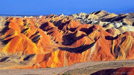 Vùng núi Zhangye Danxia nằm ở tỉnh Cam Túc của Trung Quốc, với đặc trưng là những ngọn núi có màu sắc sặc sỡ như cầu vồng. Các dải đá sa thạch đỏ tích tụ lại qua hàng triệu năm, được mô tả như lát cắt của chiếc bánh nhiều tầng. Ảnh: Alamy