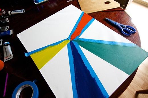 Quẹt vài vạch màu lên khung tranh trắng và 'tô điểm' bằng cách dán những đoạn băng keo màu lên. Đẹp hay không là nhờ vào tài phối màu của bạn đấy!