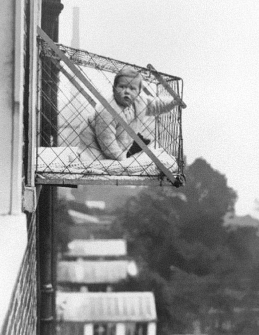 Một em bé được đặt trong một chiếc lồng ở bên ngoài cửa sổ của một căn hộ để tắm nắng vào năm 1937.