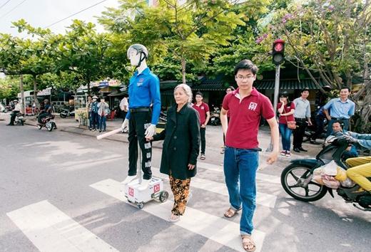 Một cụ bà được anh chàng robot mặc áo xanh tình nguyện hỗ trợ dắt tay qua đường