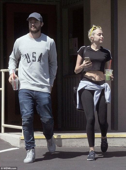 Miley mặc áo croptop khoe eo thon cùng quần bó sát gợi cảm, trên tay cầm ly sinh tố, đi bên cạnh là Patrick Schwarzenegger. Hai người trông có vẻ thoải mái và vui vẻ.