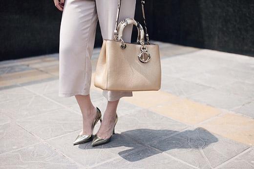 Chiếc túi xách cùng giày cao gót như một điểm nhấn với tone vàng ánh kim bắt mắt.