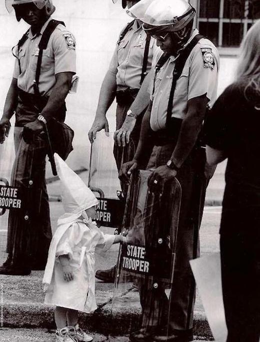 Một đứa trẻ là con của một thành viên KKK đang giơ tay chạm vào hình ảnh phản chiếu của mình trên tấm khiên của một sĩ quan người Mỹ gốc Phi trong một cuộc biểu tình năm 1992.