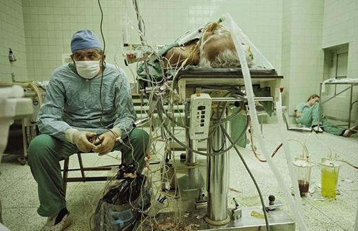 Một bác sĩ đang ngồi nghỉ sau một ca phẫu thuật cấy ghép tim kéo dài 23 giờ vào năm 1987. Trợ lý của ông thì ngủ trong góc.