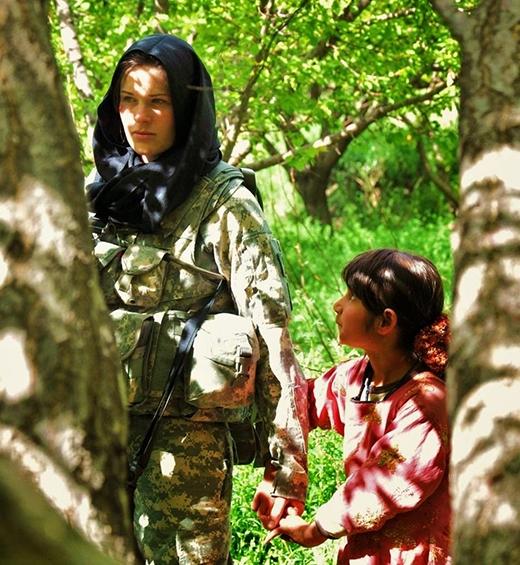 Một bé gái Afghanistan đang nắm bàn tay của một người lính Mỹ với đôi mắt tò mò.
