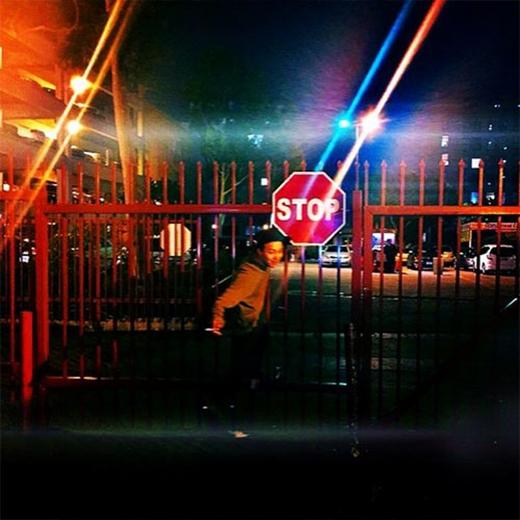 G-Dragon thích thú nghịch ngợm trước bảng hiệu STOP