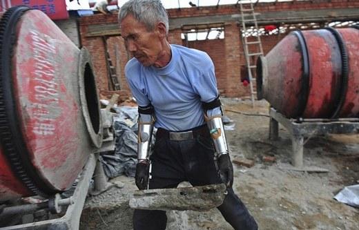 """""""Cánh tay robot"""" tự chế này có thể giúp người đàn ông bê tảng đá khá lớn. Người sáng chế ra nó – ông Sun Jifa - cũng từng bị tai nạn bom mìn khiến cánh tay ông bị mất đi, và đây chính là lí do vì sao """"cánh tay robot"""" ra đời."""