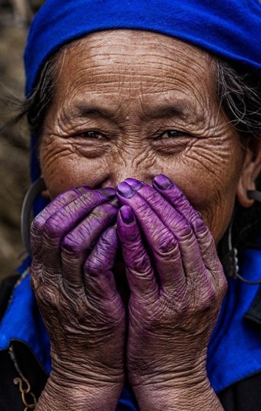 Đôi bàn tay của người phụ nữ nhuốm màu vải nhuộm, gương mặt hằn lên dấu hiệu tuổi tác nhưng đôi mắt vẫn sáng ngời.