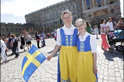 Hai cô bé Christine Bernhardt và Charlotte đến từ Heidelberg, Đức mặc trang phục truyền thống của Thụy Điển, hòa chung với dòng người để ăn mừng lễ cưới hoàng gia
