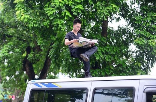 Chàng trai 9X ngồi một chân, trên tay đọc tờ báo giấy, phía dưới Nam không có vật gì.