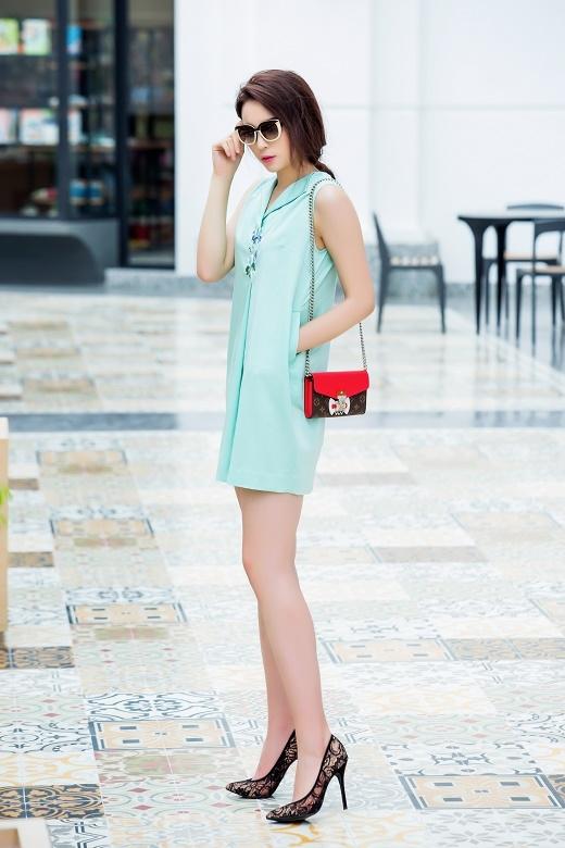 Chiếc túi đeo nhỏ xinh với hai gam màu đỏ, nâu nổi bật lên giữa sắc xanh của bộ trang phục.