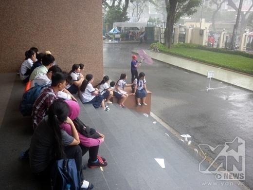 Các thí sinh thi ở dãy phòng khác ngồi chờ mưa tạnh để vào thi