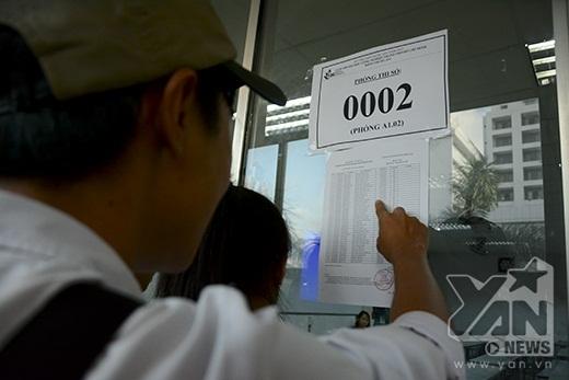 Các thí sinh theo dõi bảng tên trước phòng thi.