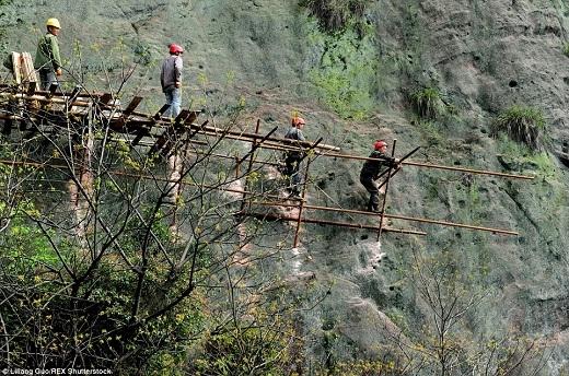 Ở đây, những người công nhân phải đứng trên giàn giáo cũ kĩ để xây dựng một con đường bao quanh vách núi.