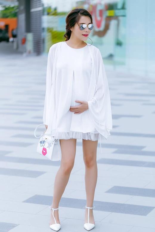 Mặc dù sắp đến ngày sinh nở nhưng Kiwi Ngô Mai Trang vẫn cực kì cá tính và sành điệu. Trong một buổi dạo phố, cô chọn chiếc váy phom rộng khéo léo che đi bụng bầu ở tháng thứ 8. Chất liệu voan lụa mềm mại càng làm tăng thêm vẻ điệu đà, nữ tính nhưng không kém phần sang trọng. Phụ kiện đi kèm gồm kính mặt gương ánh bạc cùng túi xách Shy Girl cùng tông màu với trang phục.