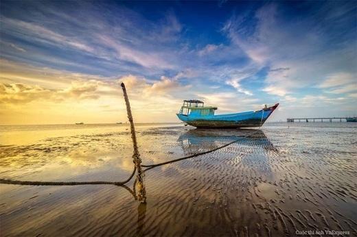 Con thuyền của ngư dân nằm nghỉ ngơi trên bãi biển Tân Thành, Gò Công trong ánh bình minh.
