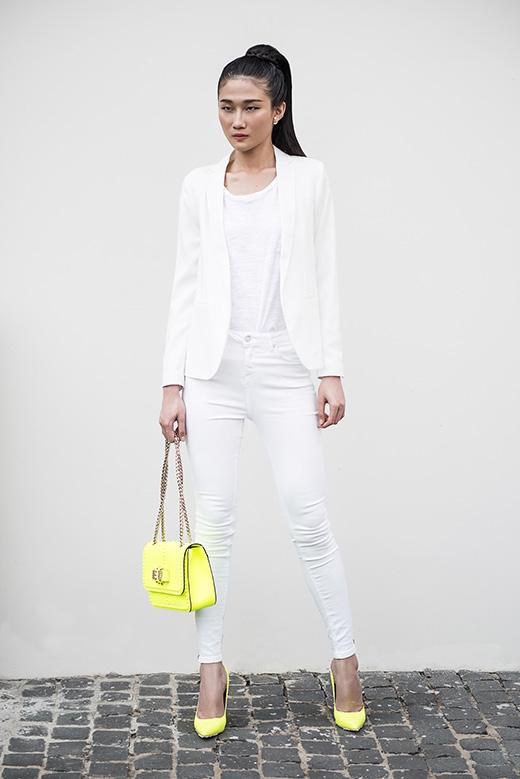 Cả cây trắng thanh lịch kết hợp giữa áo phông mỏng tang, quần jeans bó sát và áo vest khoác ngoài đượcKha Mỹ Vântạo điểm nhấn bởi tông màu vàng chanh nổi bật của giày cao gót mũi nhọn và túi xách xinh xắn.