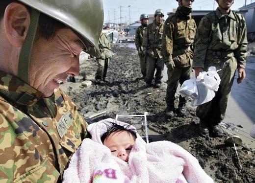 Em bé 4 tháng tuổi sống sót thần kì sau khi mất tích 4 ngày trong trận sóng thần ở Nhật Bản đang nằm ngoan ngoãn trong vòng tay của người lính thuộc lực lượng cứu hộ.
