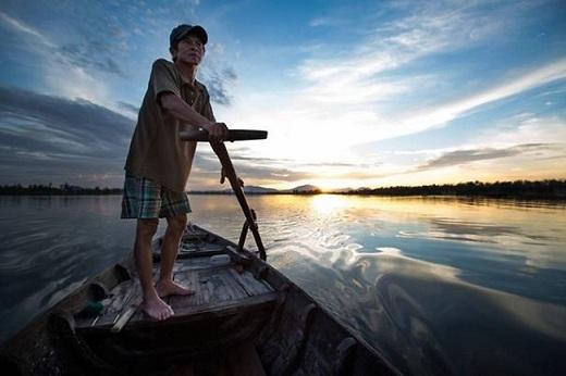 Mặt trời dần ló dạng, sông nước bốn bề mênh mông càng làm rõ tầm vóc và vẻ đẹp của người lái đò này.