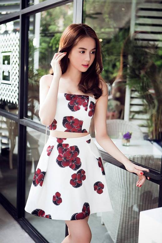 Ngọc Trinh khoe khéo vòng eo thon gọn trong chiếc áo crop top cúp ngực diện cùng chân váy xòe ngắn. Họa tiết những bông hoa với sắc đỏ tím nổi bật trên nền trắng thanh khiết.