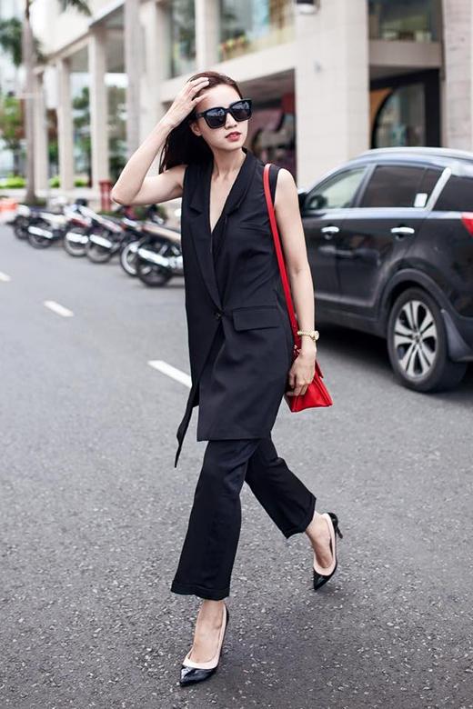 Cả cây đen của Ninh Dương Lan Ngọc được tạo điểm nhấn bởi chiếc túi đeo tông đỏ nổi bật.
