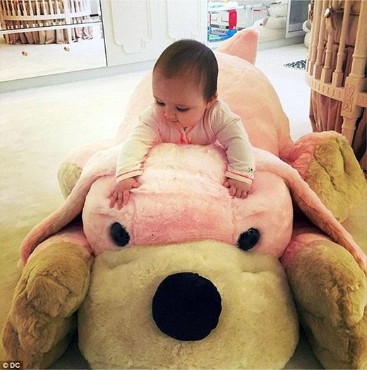 Sophia đang chơi đùa bên cạnh con gấu bông yêu thích của cô bé.