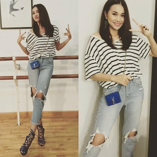 Áo kẻ sọc trễ vai được chân dài 1m12 chọn diện cùng quần jeans rách cổ điển. Chiếc túi đeo chéo nhỏ xinh cùng giày cao gót dạng lưới thể hiện trọn vẹn nét đáng yêu, ngọt ngào của nữ giám khảo quyền lực Vietnam's Next Top Model 2015.