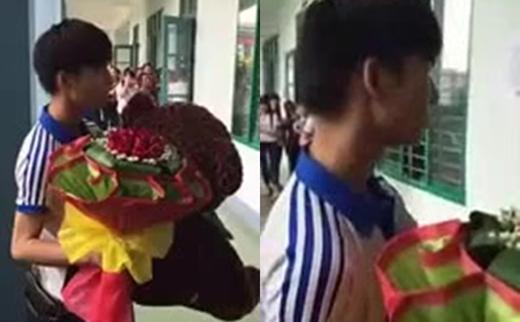 Nam sinh ôm bó hoa và gấu bông đứng ngập ngừng trước lớp học.