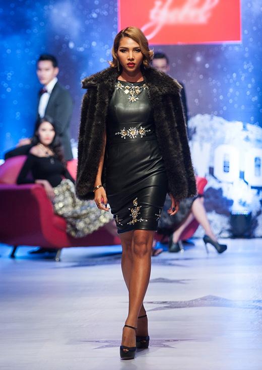 Minh Triệu mở màn ấn tượng trong chiếc váy đen ôm sát trên nền chất liệu da bóng đính kết họa tiết. Bộ trang phục này được kết hợp cùng áo lông dày mang đậm hơi thở của thời trang Thu - Đông.