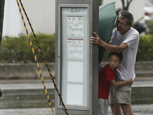Hai ông cháu phải núp vào cột điện để tránh gió giật mạnh.