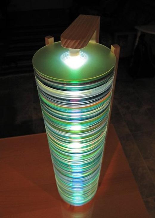 Nếu muốn đơn giản hơn, bạn chỉ cần chồng hết tất cả những đĩa CD lại với nhau và cố định bằng keo. Đừng quên công đoạn cuối cùng là tìm một chiếc đèn có cùng chiều dài để đặt vào trong nhé. Vậylà có ngay một chiếc đèn ngủ bắt mắt rồi.