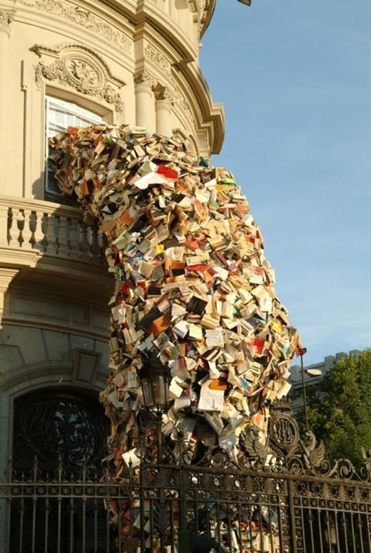 Họa sĩ người Tây Ban Nha Alicia Martin đã tạo nên một dòng chảy với hàng ngàn cuốn sách từ ô cửa sổ xuống mặt đường gây sửng sốt cho người qua lại.