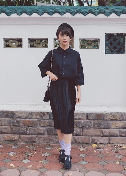 Cả cây đen cực chất gồm áo sơ mi liền tay, chân váy xếp li điệu đà mang đến vẻ ngoài thanh lịch pha chút trầm mặc, sâu lắng.