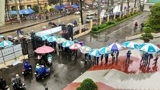 Bất chấp trời mưa, trời nắng, các bạnsinh viên tình nguyện đứng hàng dài che ô cho các thí sinh tới dự thi tốt nghiệp.