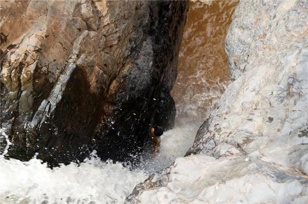 Bé trai bị rơi xuống thác nước chảy xiết rất nguy hiểm.
